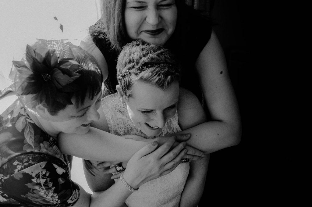 bride being hugged by her girls