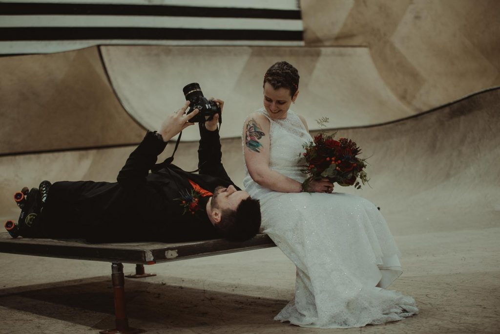 groom taking a photo of his wife
