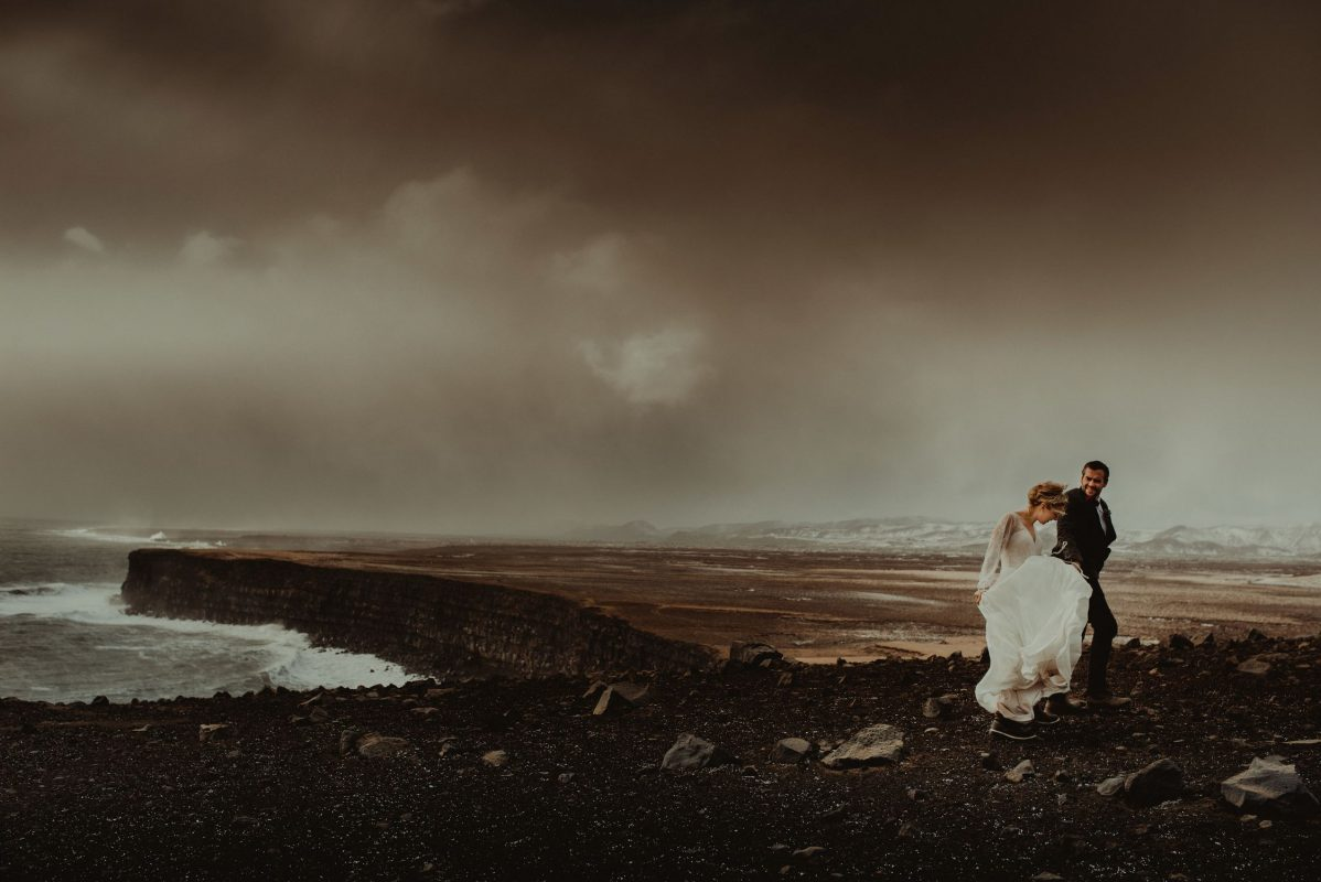 Iceland wedding portrait of a couple running next to a cliff