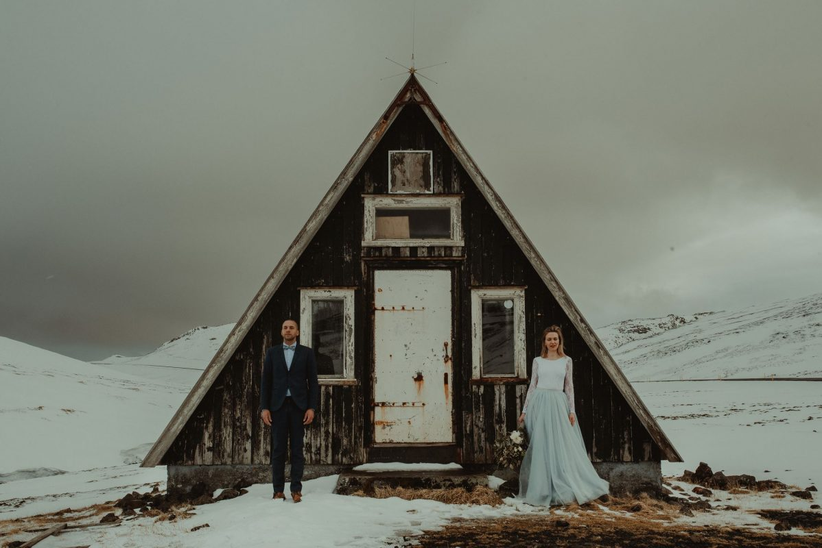 Couple standing by a house on an Iceland glacier