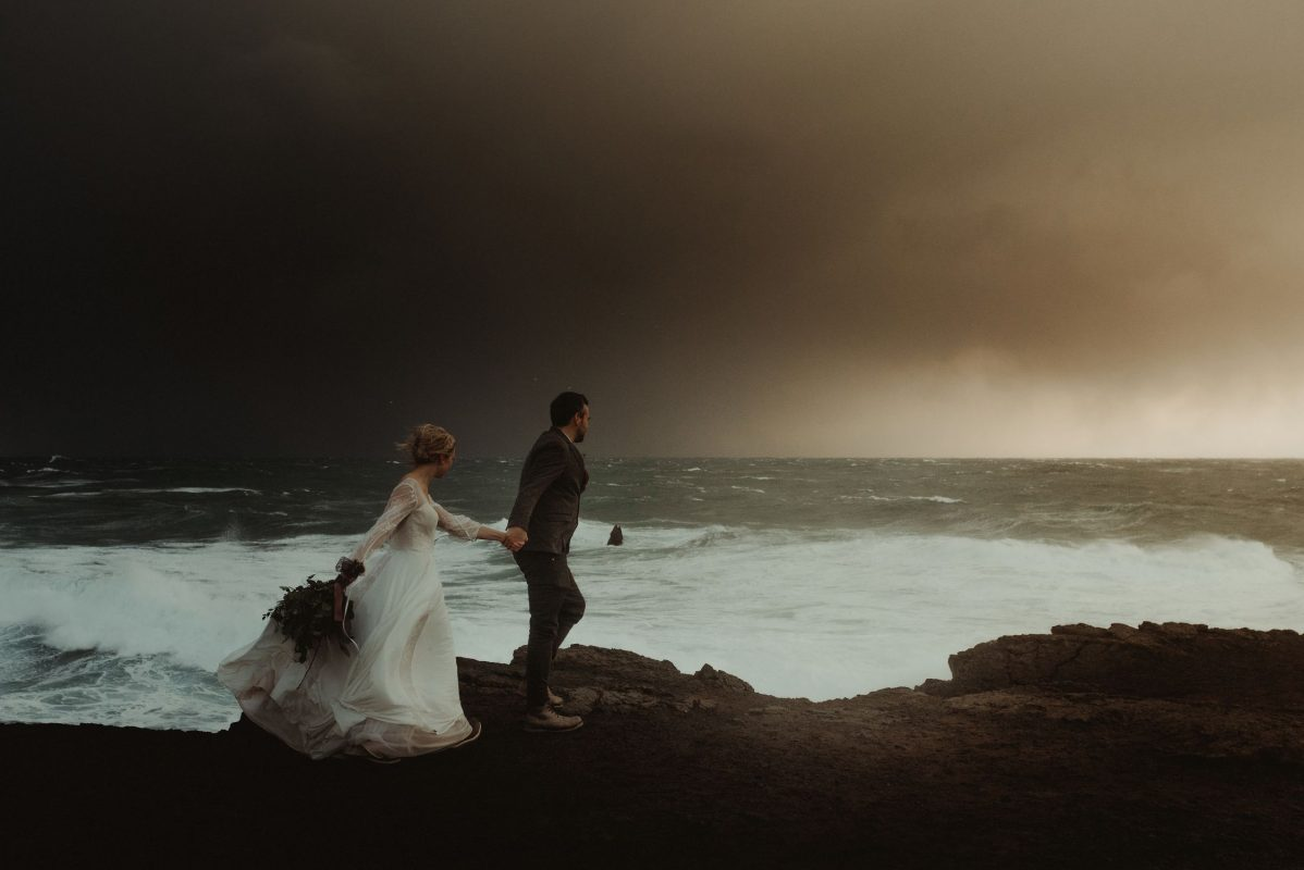 Dramatic Iceland wedding portrait of a couple posing by the waves