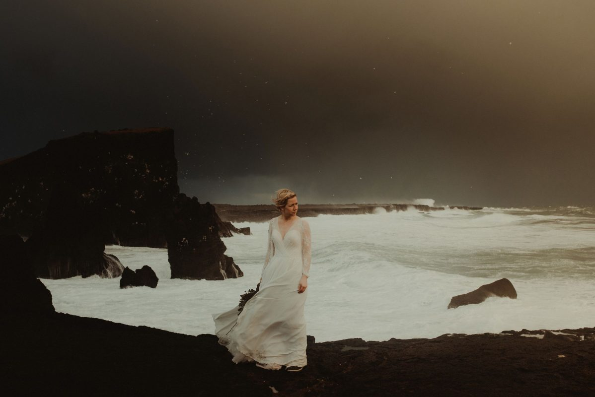 Dramatic Iceland wedding portrait of a bride posing by the waves