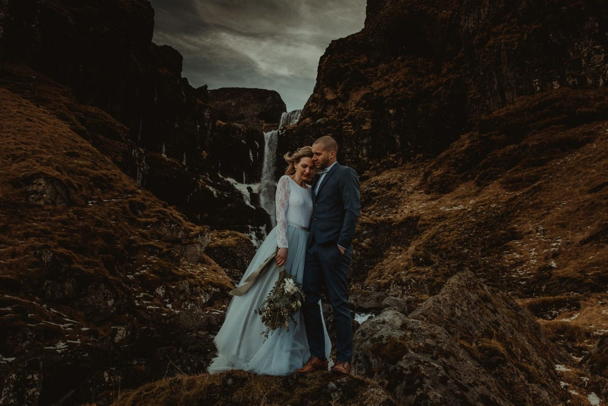 wedding couple standing next to iceland waterfall