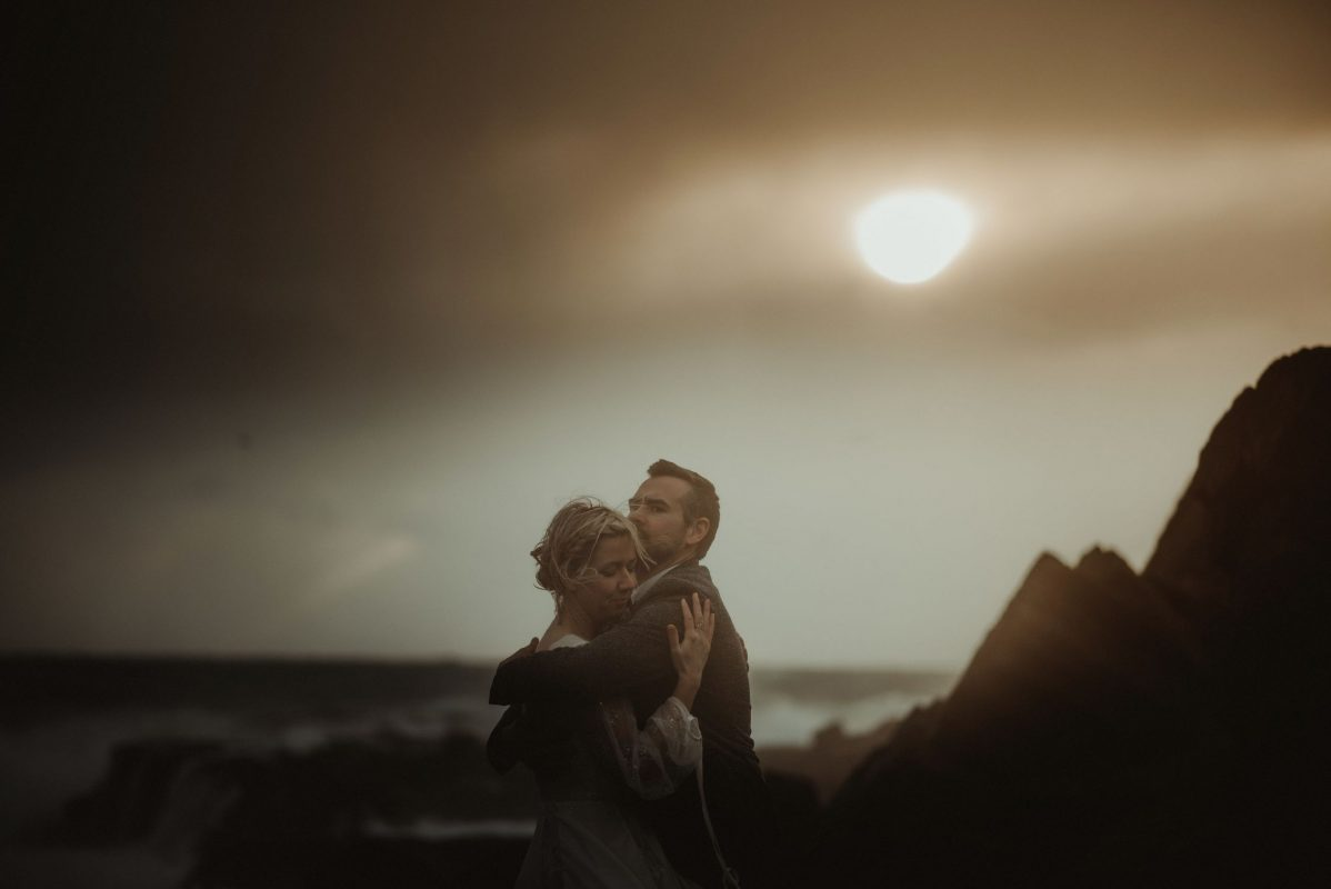 Dramatic Iceland wedding portrait of a couple posing in a sunset