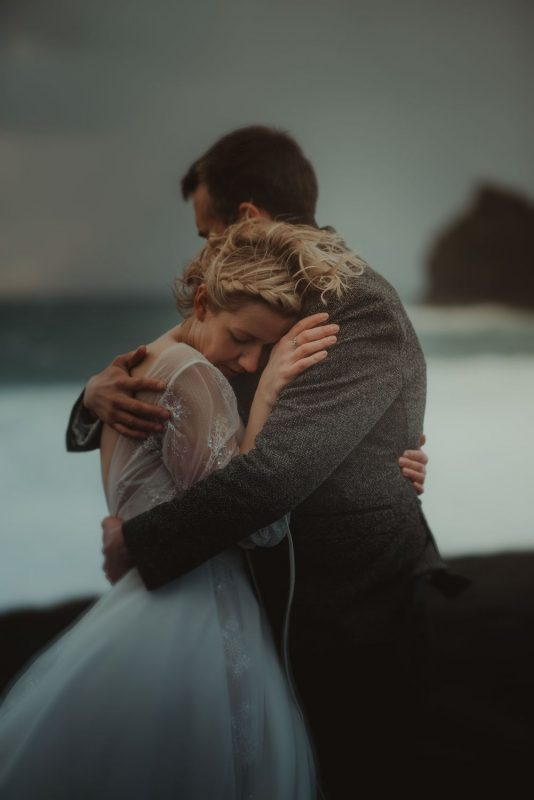 Dramatic Iceland wedding portrait of a couple posing in cold weather