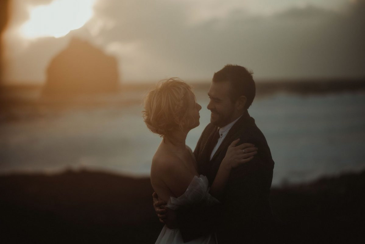 Dramatic Iceland wedding portrait of a couple posing in cold weather by the cliffs