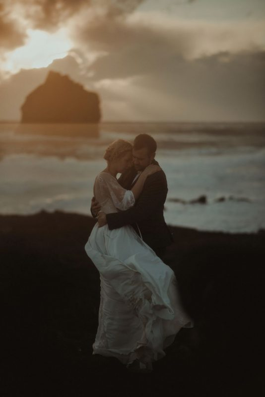 Dramatic Iceland wedding portrait of a couple posing in cold weather at sunset by the cliffs