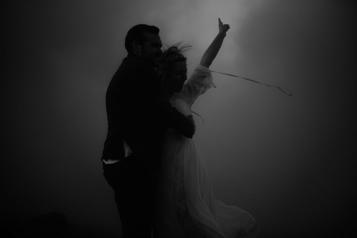 Wedding portrait of a couple in Iceland kissing in the smoke of a geysir