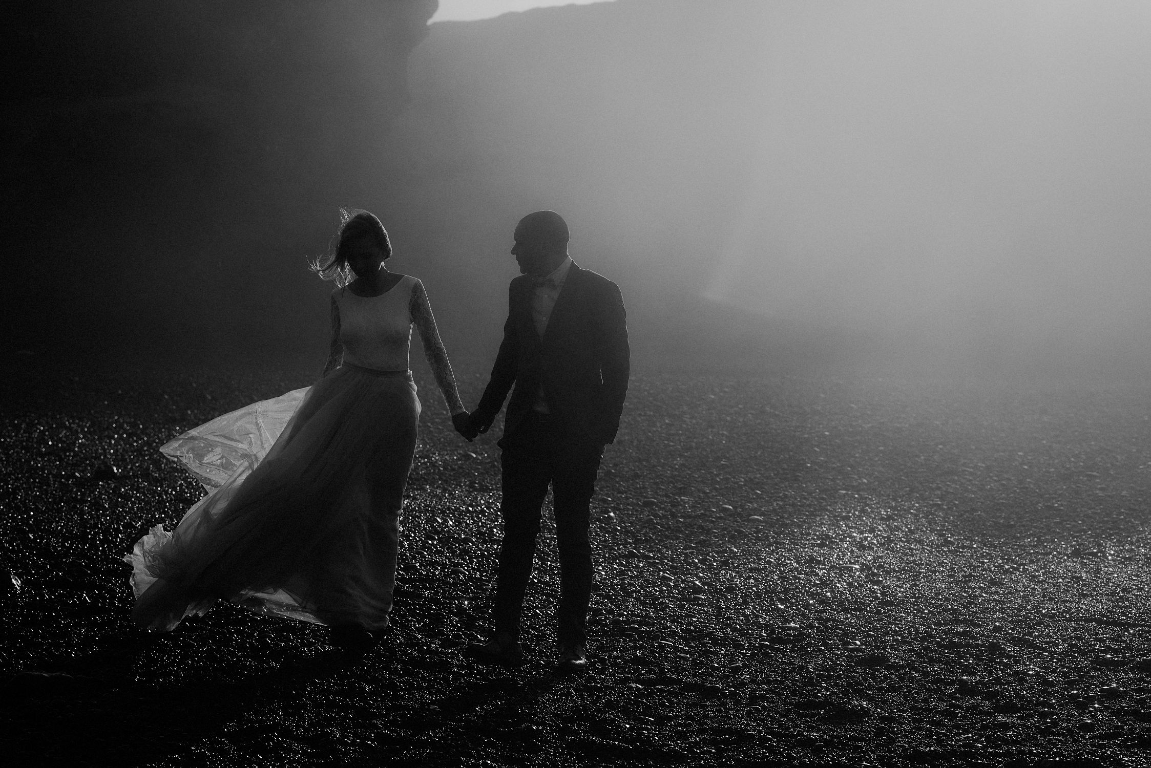 Snaefellsnes bride and groom walking on the beach black and white