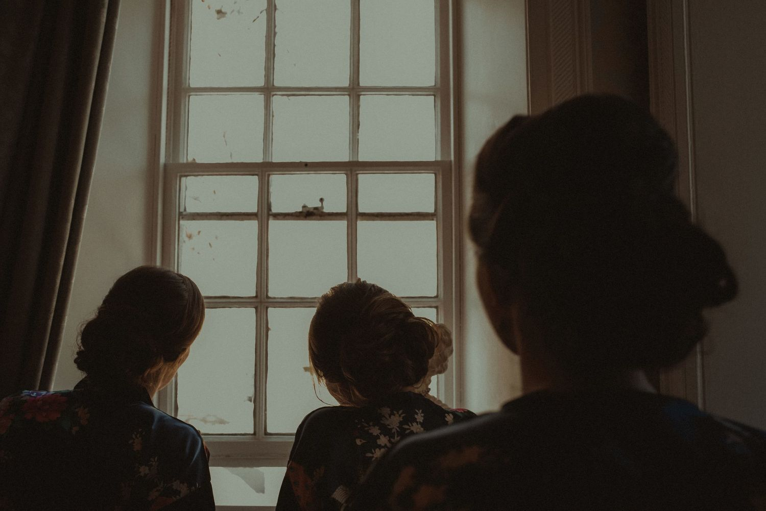 Bridesmaids looking through the window at Elsick House Wedding