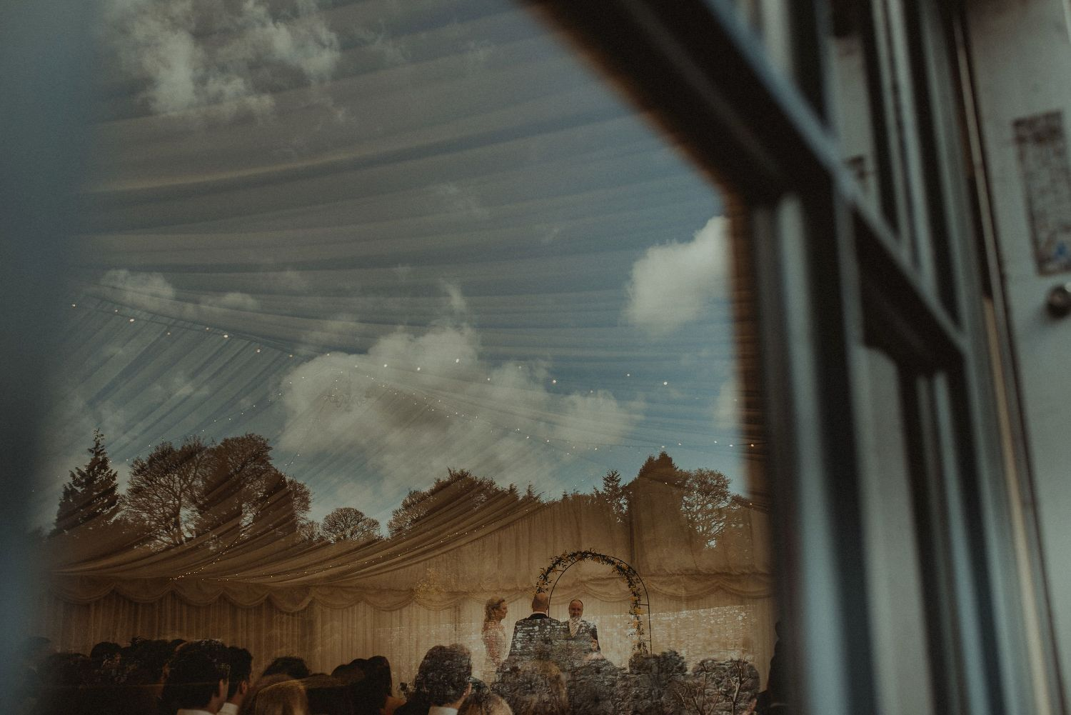 Reflection in wedding marquee window at Elsick House