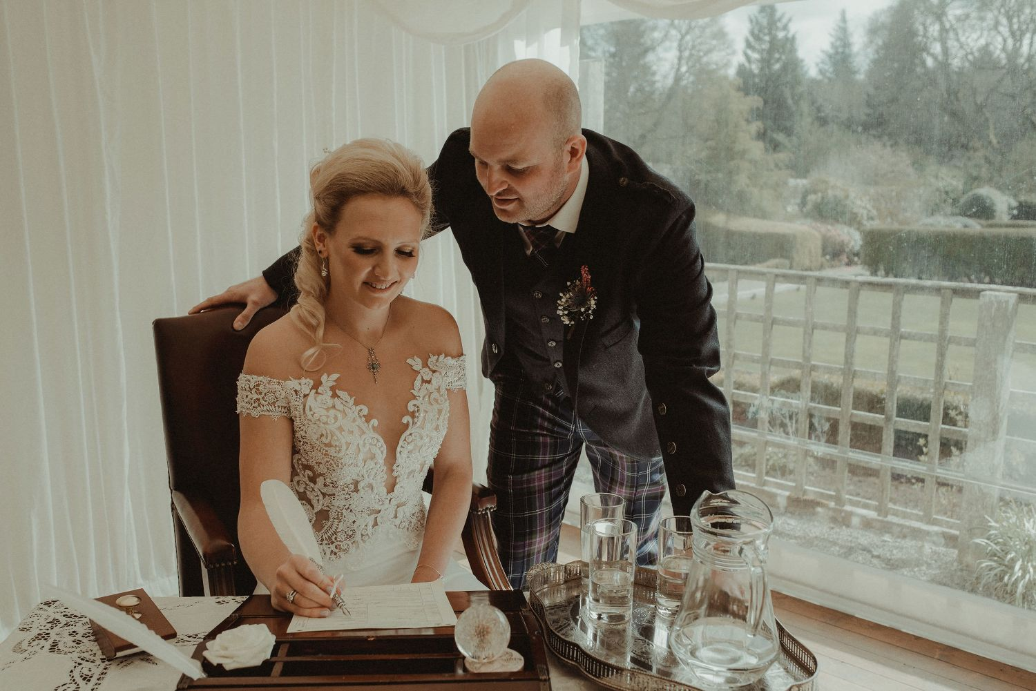 Bride and groom signing the wedding register at Elsick House